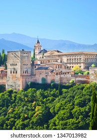 Vertical picture of beautiful Alhambra Palace complex in Granada, Spain. The amazing sample of Moorish architecture is surrounded by woods and mountains. Taken with blue sky above.
