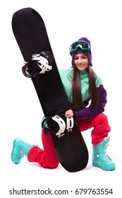 vertical picture, isolated on white, attractive caucasian girl in purple ski outfit, red trousers and purple wool hat, hold black snowboard, look at camera, stand on one knee