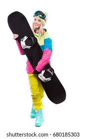 vertical picture, isolated on white, attractive  young caucasian girl in colorful ski outfit, blue snow boots and yellow trousers hold black snowboard