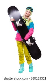 vertical picture, isolated on white, blonde pretty young caucasian woman in colorful ski outfit, yellow trousers and blue snow goggles hold black snowboard, look at camera