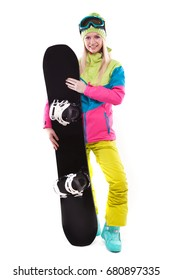 vertical picture, isolated on white, attractive  young caucasian girl in colorful ski costume, yellow trousers and blue ski glasses hold black snowboard, stand behind snowboard