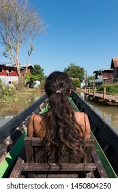 Vertical picture of long hair, brunette woman looking the small village during boat trip in Inle Lake, Myanmar