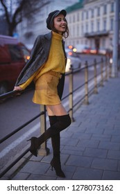 vertical portrait of a beautiful fashionable stylish woman in bright yellow sweater and skirt, black high heel boots and cap walking and posing outdoors at evening, street style shooting