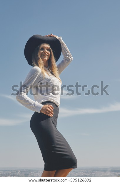 Vertical portrait from below of a young smiling woman dressed in white blouse and black knee length skirt wearing wide-brim hat