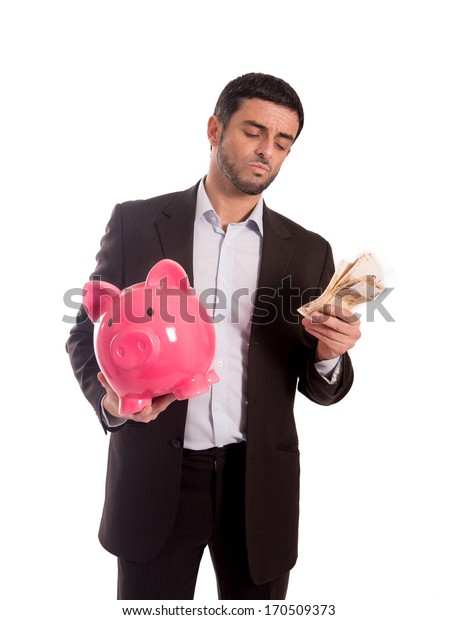 vertical portrait of a business man wearing a suit holding a piggy bank and money thinking about saving and his future