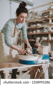 Vertical portrait of charming craftswoman kneading and shaping clay in pottery workshop