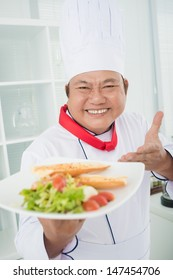 Vertical portrait of a cheerful chef-cook showing his tasty dish