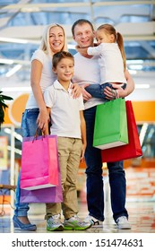 Vertical portrait of a cheerful family standing together holding shopping-bags