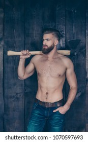 Vertical portrait of confident strong manful fearless severe powerful erotic muscles muscular ideal handsome attractive focused woodsman carrying steel arms on shoulder isolated on wooden background