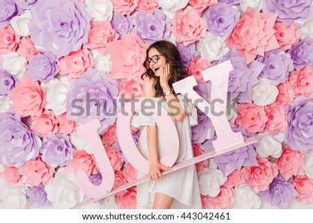 Vertical portrait of cute brunette girl. She stands and holds wood word JOY smiling widely. She has curly hair and wears white dress off the shoulder and black glasses. Background in pink flowers.