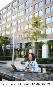 Vertical portrait of distance, young queer girl waiting for her girlfriend outside campus, browsing internet, prepare project for class as working outdoors with laptop, using mobile phone casually