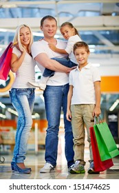 Vertical portrait of a family of four enjoying doing shopping
