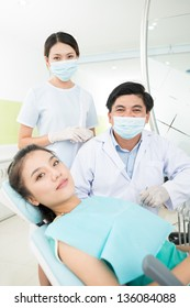 Vertical portrait of a female patient and two professional dentists