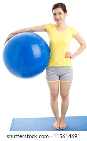 Vertical portrait of a fit young woman holding a huge exercise ball
