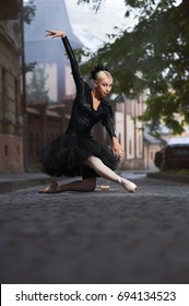 Vertical portrait of a gorgeous young ballerina wearing black corset and tutu dancing expressively on the street of an old town.