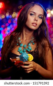 Vertical portrait of a gorgeous young woman holding a cocktail