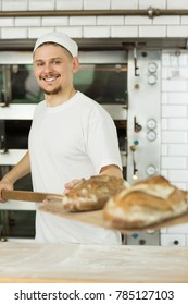 Vertical portrait of a handsome young male baker smiling posing with bread on the shovel taken out of the oven profession occupation employment career cooking chef pastry organic nutrition eating