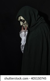 Vertical portrait image of a man in a mask and hooded cloak.