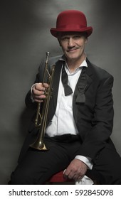 Vertical portrait image of a mature jazz man with a trumpet
