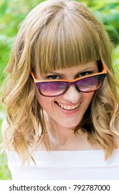 Vertical portrait of laughing woman with blond hair in sunglass