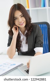 Vertical portrait of a lovely female office worker at her workplace