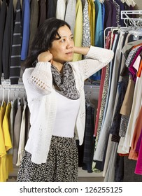 Vertical portrait of mature Asian woman in walk-in closet putting on her scarf