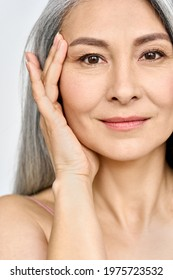 Vertical portrait of middle aged Asian woman's face with perfect skin. Older mature lady touching pampering face with hand. Advertising of cosmetology salon rejuvenating spa procedures skincare.