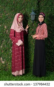 Vertical portrait of muslim women in national clothing standing outside
