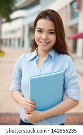 Vertical portrait of a smiling student with a notepad in hands