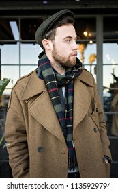 Vertical portrait of stylish young man with light beard posing with confidence outdoors. Gentleman wears british style scarf and brown coat with flat cap looking to side.
