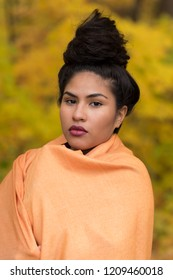 Vertical portrait of sultry hispanic young woman with hair up in a high bun draped in an orange shawl in front of soft focus Fall foliage