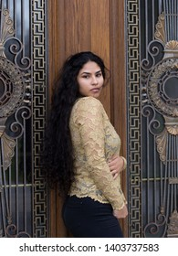 Vertical portrait of sultry hispanic young woman with windblown long curly dark hair and wearing elegant gold lace top and tight black jeans while looking away from a patrimonial door