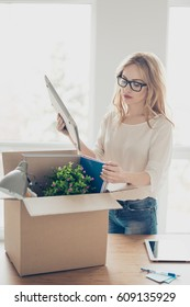 Vertical portrait of upset fired woman in glasses packing up her stuff into cardboard box at office.