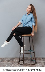 Vertical portrait of Woman in shirt posing on chair in studio. Isolated gray background