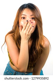 vertical portrait of young shocked and surprised beautiful Asian Korean woman covering mouth with hand in disbelief and surprise face expression isolated on white background