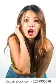 vertical portrait of young shocked and surprised beautiful Asian Korean woman with mouth opened in disbelief and surprise face expression isolated on white background