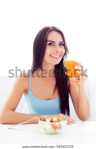 A vertical portrait of young smiling beautiful woman sitting at the table eating salad and drinking orange juice