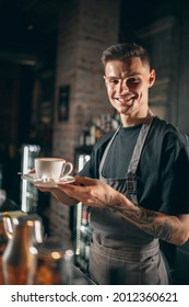 Vertical portrait of young smiling caucasian male barista serving hot aromatic coffee, cappuchino of latte in a white cup with marshmallow enjoying his job.