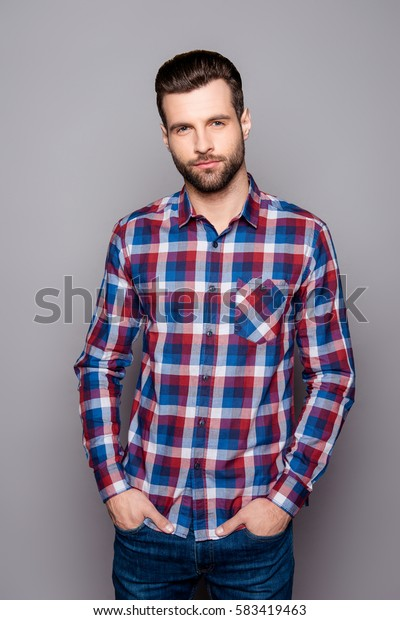Vertical portrait of young stylisg guy in checkered shirt holding hands in his pockets