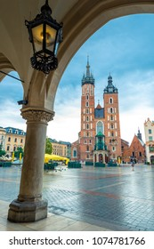 Vertical postcard view of the main square of Krakow. Mary's church and arch in cloudy weather
