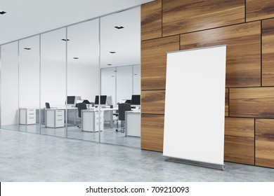 Vertical poster is standing on a gray office floor near a light wooden wall in a lobby. Open space office is to the left. Side view. 3d rendering mock up