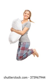 Vertical profile shot of a blond woman holding a pillow and jumping isolated on white background