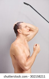 Vertical profile shot of a young man taking a shower on gray background