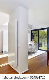 Vertical radiator on a column in a spacious apartment with french windows and lush garden