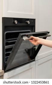 Vertical and real photo of woman hand opening door of new black built-in oven in white kitchen cabinet