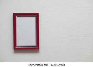 Vertical red plastic frame on indoor white wall