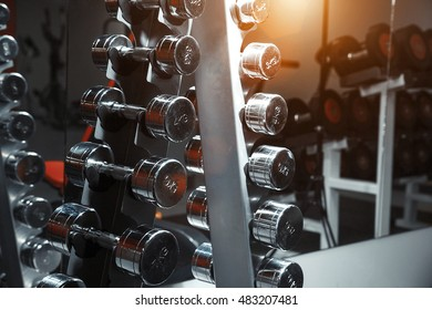 vertical row of chrome dumbbells on rack in gym. CloseUp.