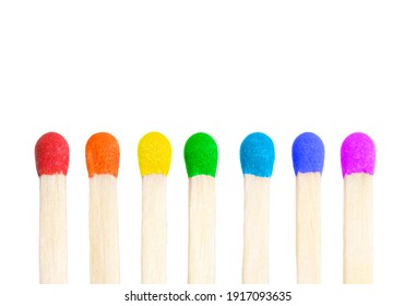 Vertical row of seven matches with match heads painted in rainbow colors isolated on white background.