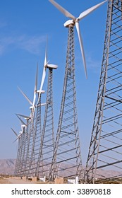 vertical of a row of wind turbines against a blue sky