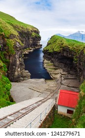 Vertical scenery image of natural harbour gorge nearby idyllic village Gjogv, most northern village of Eysturoy, Faroe islands